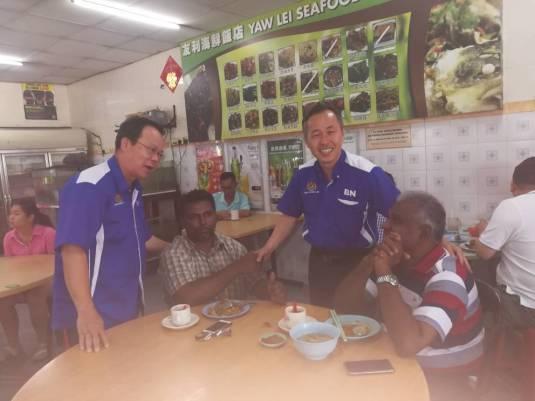 陈松霖(右二)和颜明富(左)与在餐室用餐的居民交流。