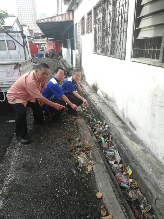 陈松霖(右起),颜明富和叶锦英指着阻塞的後巷沟渠。