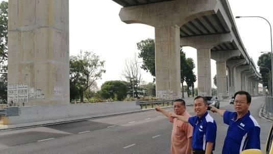 颜明富(右起),陈松霖和叶锦英指着拆了後又被贴在柱子上的阿窿广告。